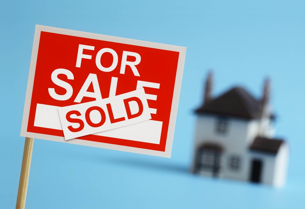 Real estate agent for sale sign with sold sticker and house in background